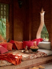 a chic sofa with colorful and patterned textiles plus a tray with a traditional tea pot and cups