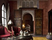 a moody Moroccan living room with beautiful doors, a decorative window, and traditional teaware