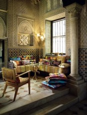a gold Moroccan space with a super colorful L-shaped sofa and bright pillows, mosaic walls and beautiful chairs