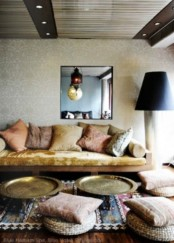 a neutral Moroccan space with colorful and patterned textiles and traditional lamps