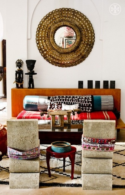 a neutral living room with a colorful sofa and pillows, an ornate mirror and rugs