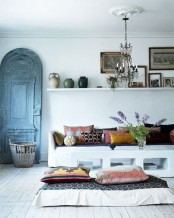a white Moroccan living room with colorful pillows, teaware, a vintage door and accessories