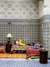 a fully mosaic tile lviing room with a colorful sofa and pillows and carved tables will make your jaw drop