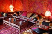 a super bright living room with fabric covered walls, bright textiles and a carved table in the center