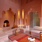 a bright Moroccan living room with cutout niches, a colorful rug and hexagonal coffee tables