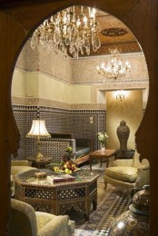a formal Moroccan space in gold and black, with mosaics, carved furniture and tiles on the walls