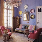a colorful Moroccan living room with bright furniture, an ornate screen and decorative plates on the wall