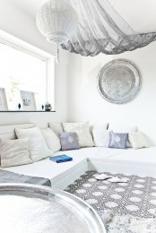 a pure white Moroccan living room with a mosaic floor, an L-shaped sofa, a traditional lantern and a hammered plate on the wall