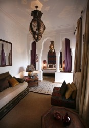 a Moroccan living room with carved wood furniture, pillars, a traditional lantern and a cozy alcove with a bed