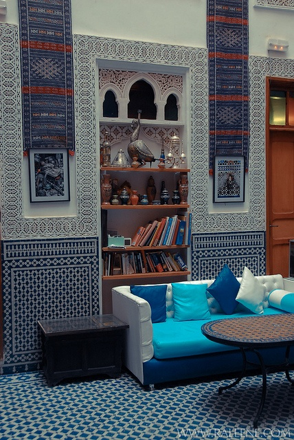 a bright Moroccan living room done with mosaic tiles, artworks and colorful furniture