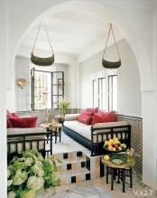 a neutral living room in an alcove, unique pendant lanterns and carved coffee tables