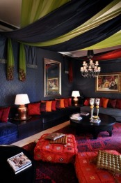 a very bright Moroccan living room with lots of printed textiles all over, accessories and pillows and carved coffee tables