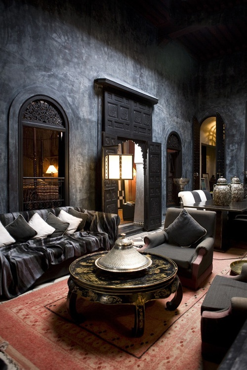 a dark and moody Moroccan space with orante doors and windows and a gorgeous metal coffee table
