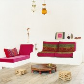 a neutral Moroccan living room done with colorful printed textiles, pendant lamps and low tables
