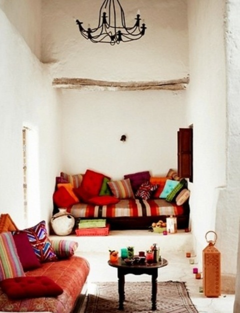 a white living room with plaster walls, colorful and printed textiles and pillows and traditional lanterns