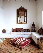 a neutral Moroccan living room with colorful and patterned pillows, a mirror and a lantern