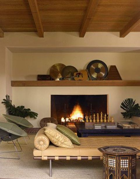 a neutral living room with carved chess by the fireplace and a carved coffee table that hint on Moroccan style