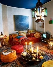 a colorful Moroccan living room with pillows, textiles, lanterns, candles and ottomans