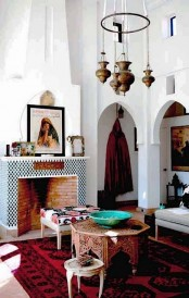 a rather neutral Moroccan living room with carved coffee tables, pendant lamps and bold textiles