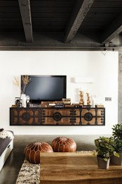 a neutral living room with Moroccan touches – a carved and orante floatign vanity and leather ottomans