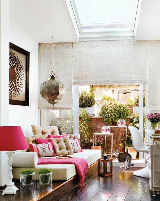 a chic neutral living room with touches of pink, an artwork and a cool pendant lamp