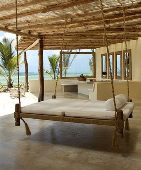 a hanging bed fully covered with jute rope and hanging on it and with white cushions is ideal for tropics
