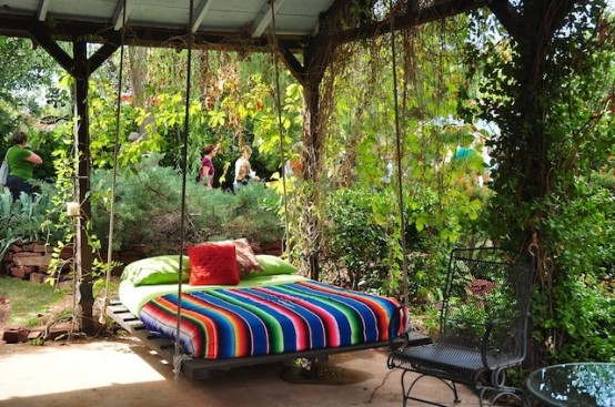 a dark stained wooden hanging bed with ropes and colorful bedding to remind that this is summer