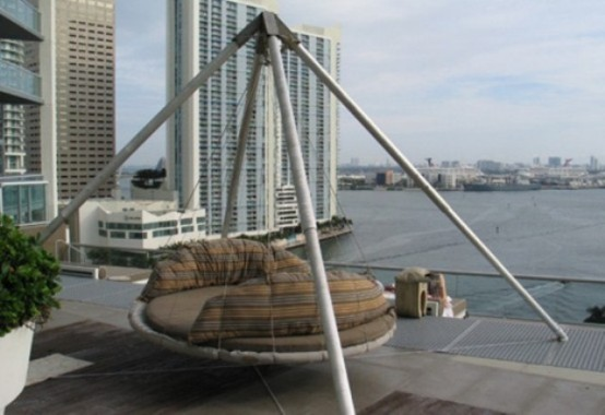 a metal hanging bed with a large base and ropes with striped pillows and cushions and a gorgeous view