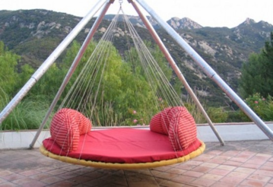 a round hanging bed with a proper base and red cushions and pillows is a cool idea for any outdoor space