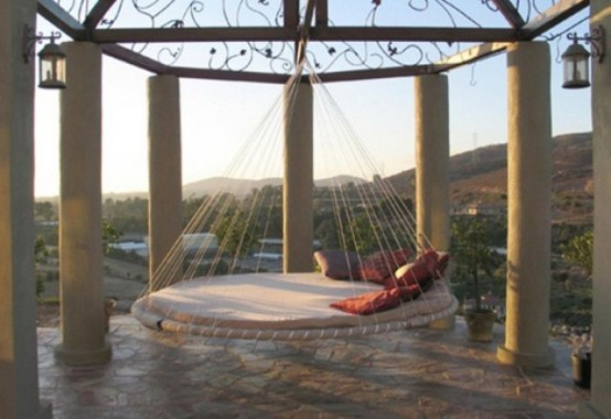 a round hanging bed with ropes and pillows hung in a gazebo is a great way to highlight this bed