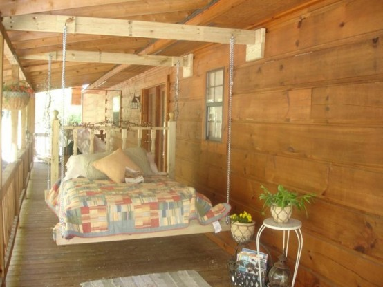a hanging bed on chains on wooden beams will make your porch or patio super welcoming