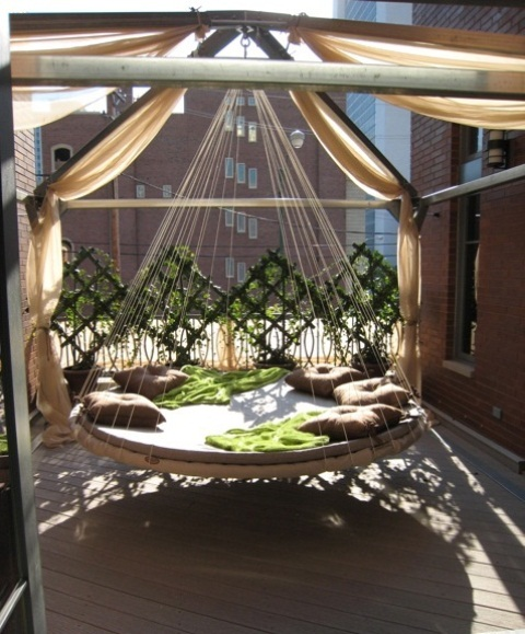 a round hanging bed on ropes with pillows and blankets makes up a gorgeous relaxing spot