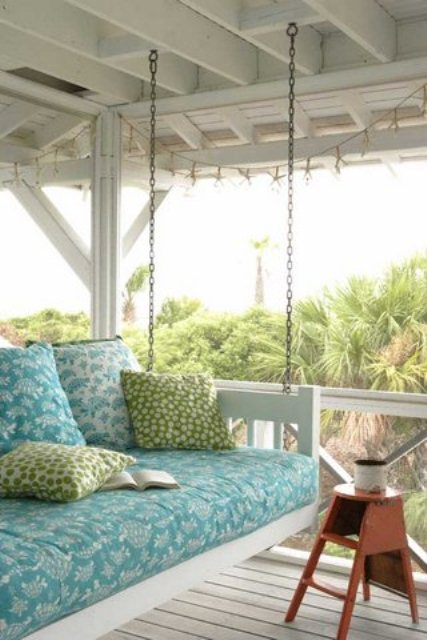 a comfortable white hanging bed with blue and green bedding is a cool idea for a rustic or vintage porch
