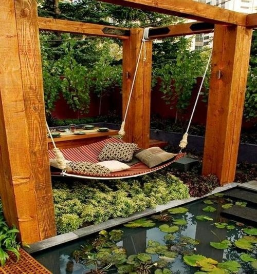a zen relaxing space with a wooden gazebo and a hanging bed of pallets with some pillows next to a pond is very peaceful