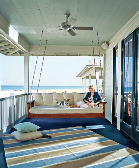 a hanging upholstered bench on chains is a cool idea for a nautical porch, you can enjoy the views here