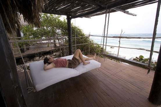 a hanging bed on ropes with a white cushion will let you lie on it and relax whenever you want