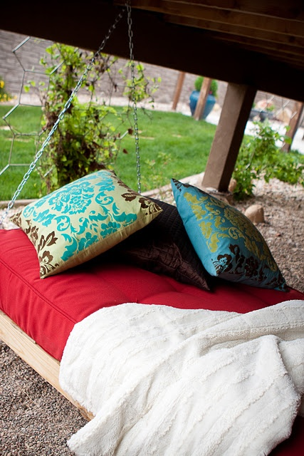 a simple hanging bed on chains with colorful bedding, blankets and pillows is a cool idea for every outdoor space