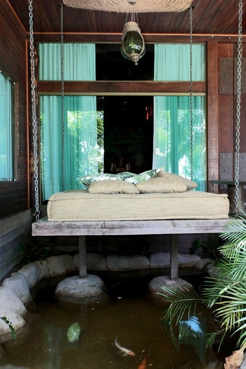 a whitewashed wooden bed hanging on chains is a cool idea for many outdoor spaces and can be hung over a pond
