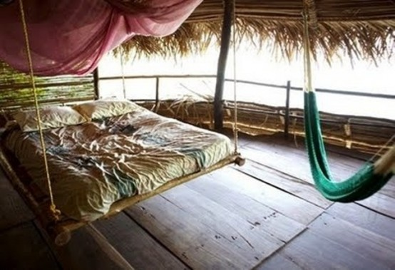 a hanging bamboo bed on ropes is ideal for a tropical outdoor space, it perfectly highlights the esthetics of the space