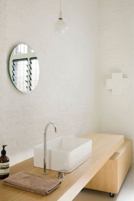 a neutral Scandinavian bathroom with white tiles, a light-colored wooden vanity and a pendant bulb