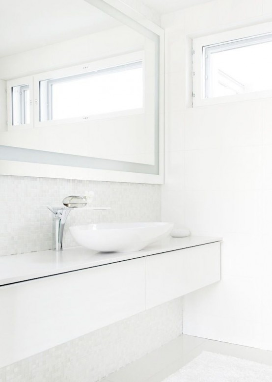 a fresh Nordic bathroom with a long sleek vanity, a large mirror and a bowl sink