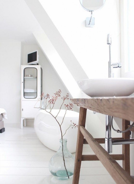 a beautiful Nordic bathroom with an oval tub and a bowl sink, a wooden vanity and an armoire for storage