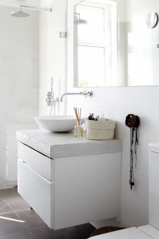 a laconic Nordic bathroom with mini white tiles on the walls and vanity, a bowl sink and a large mirror