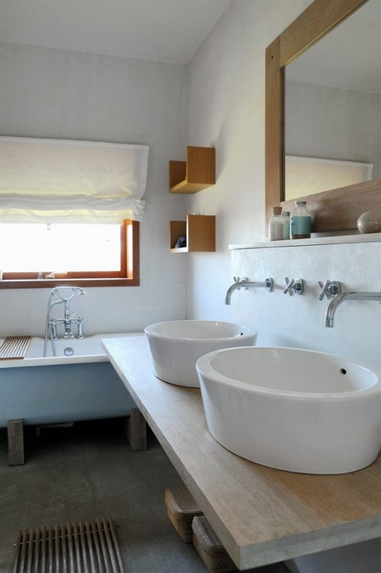 a relaxed Scandinavian bathroom with a blue vintage tub, large bowl sinks and a large mirror
