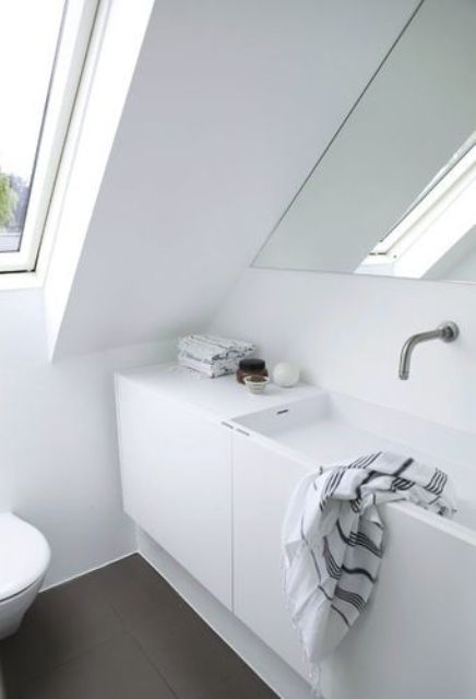 a small Nordic attic bathroom with a skylight, a built-in sink and a triangle mirror