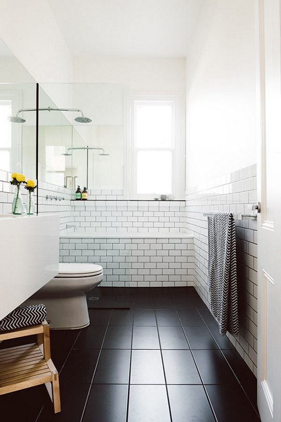a Scandinavian bathroom in black and white, with natural wood and printed towels