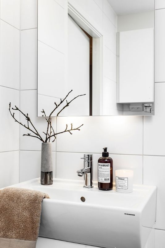 a Nordic bathroom with white tiles, a white sink, a large mirror and a branch arrangement