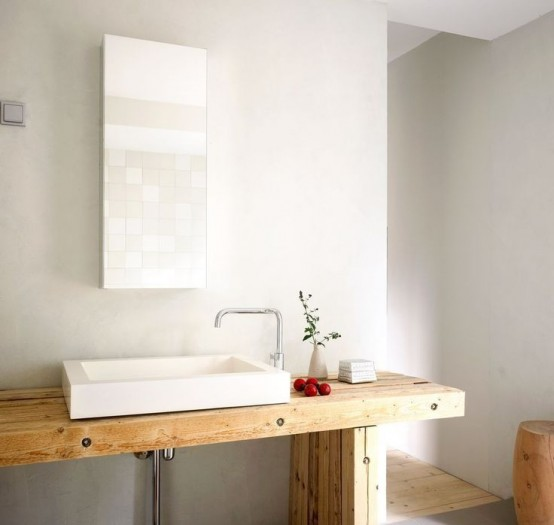 a light-colored wooden vanity, a rectangular mirror, a stool and a shower space with a wooden floor
