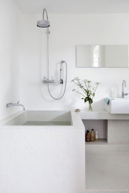 a minimalist Scandinavian bathroom in white and off-white with a tile clad bathtub and niches for storage