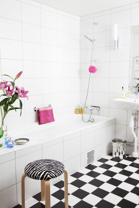 a black and white Nordic bathroom spruced up with bright pink touches and prints